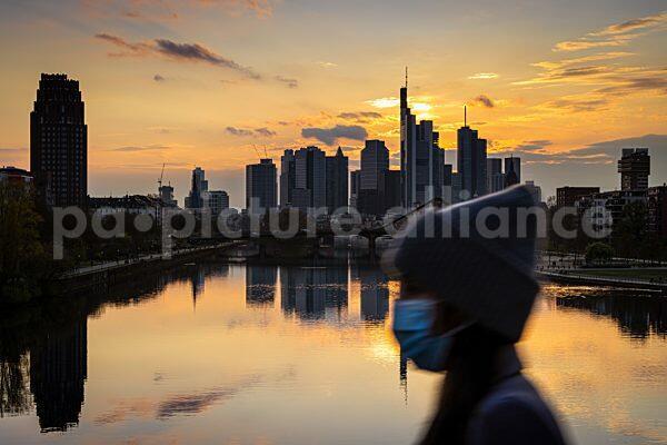 Passantin mit Schutzmaske vor der Frankfurter Skyline (18.04.2021)